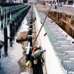 Workers Examining Side of Pier Installation